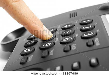 One human finger pressing key on phone