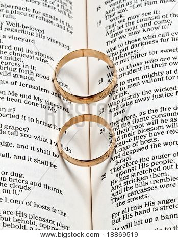 Wedding rings on a Bible with shadow shape heart