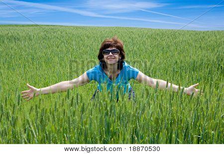 The happy woman on the wheaten field.