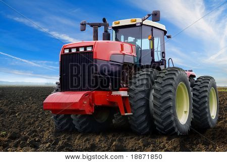 Wheel tractor on an arable land in the field.