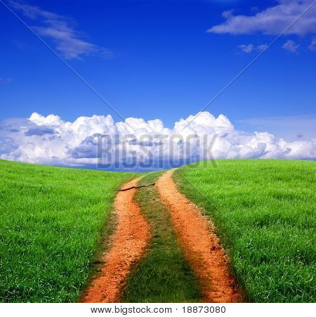 dirt road in grass and sunset