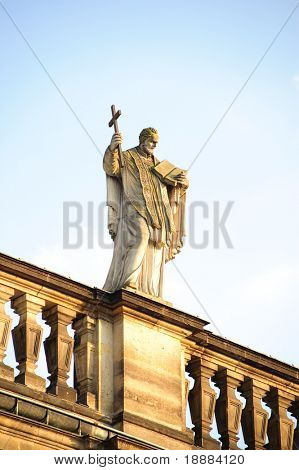 sculpture of monk with cross and holy bible