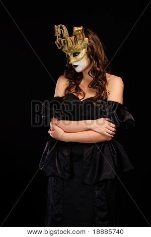 portrait of sexy woman in golden party mask isolated on black