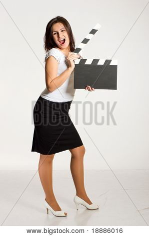 Pretty young woman holding a clapperboard