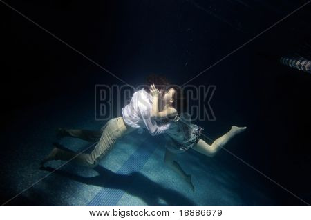 Kissing pair on bottom of swimming pool