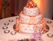 image of three tier  - Three tiered wedding cake and champagne glasses on a table - JPG