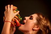 Woman eating hamburger. Student consume fast food. Portrait in profile of girl opened her mouth to t poster