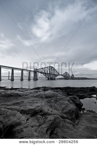 Black And White Forth Rail Bridge With Foreground Rocks In Scotland