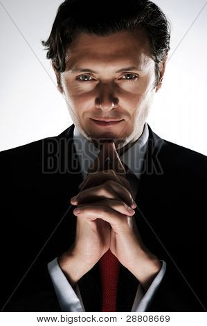 Evil looking businessman clasps his hands under his chin, in dramatic lighting
