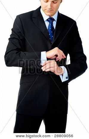 Businessman looks down to adjust his cuff links in studio, isolated on white