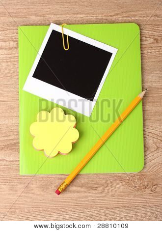 Photo paper and green notebook on wooden background
