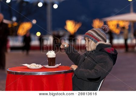 boy drinking a hot chocolate with whipped cream, outdoor portrait