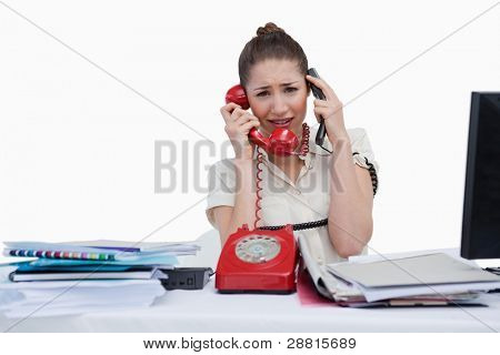 Overbooked businesswoman answering the phones against a white background