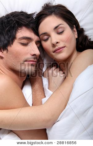 Couple snuggling in bed together