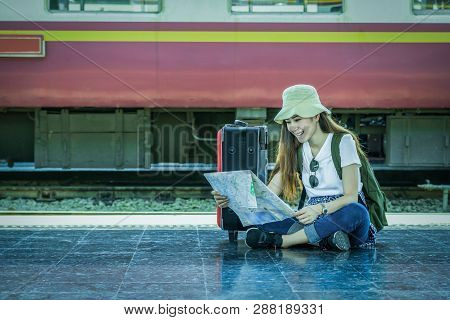 poster of Asia Woman Traveller Sitting And Looking At The Map Before Go To Travel At The Train Station, Travel