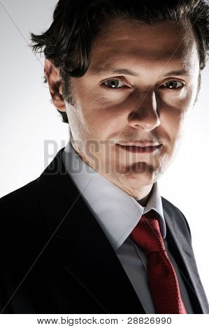 Dramatic lighting on a caucasian man in a business suit to convey a deceitful side