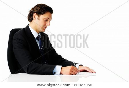 Attractive man in a smart business suit reads and signs some documents