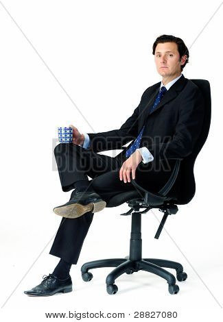 Male office worker seats in his chair, holding a mug of coffee