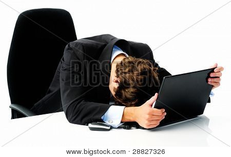 Businessman in suit puts his head down on his laptop computer when he fails to meet his target