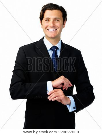 Smiling confident business man in a formal suit adjusts his cufflinks