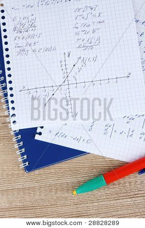 Math, physics and geometry on copybook page on a wooden table