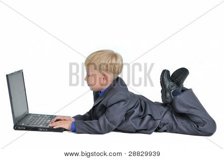 Little boy wearing suit working on laptop, isolated on white background