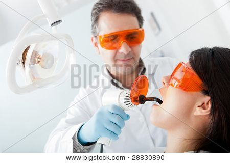 Dentist fixing a cavity on a female patient using laser
