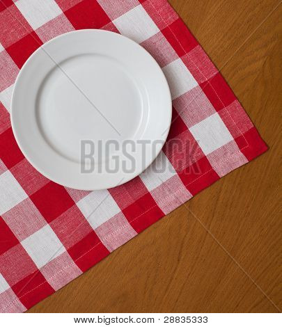 white plate on wooden table with red gingham tablecloth