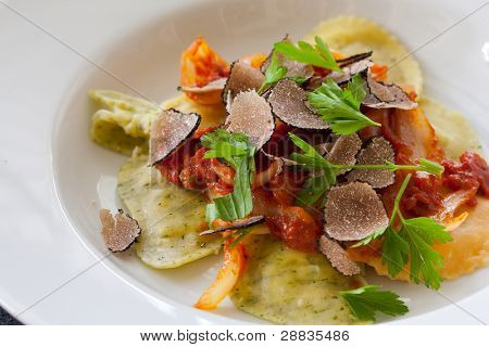 Freshly made italian ravioli pasta with slices of black truffle