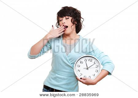 young woman holding clock and yawning. isolated on white background