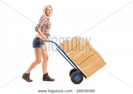 Full length portrait of a female manual worker pushing a handtruck with boxes on it isolated on white background