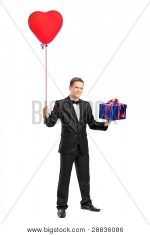 Full length portrait of a man holding a red heart shaped balloon and a gift isolated against white background