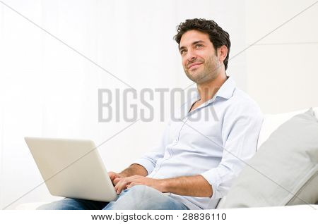 Smiling dreaming young man looking up while working at laptop computer