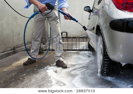 Man, wahsing his car in the stall of a car wash, using a high pressure water jet