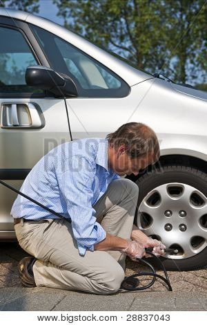 Man, kneeling at the curb, and inflating the front tyre of his car using an automated air pressure hose
