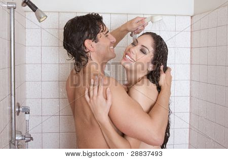 Loving affectionate nude young heterosexual couple in affectionate sensual kiss after taking shower. Mid adult Caucasian men in late 30s and young Latina woman in early 20s