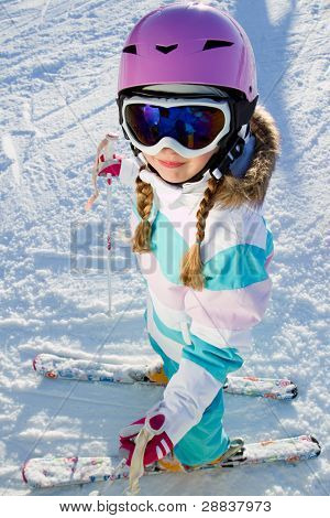 Skiing, portrait of beautiful young skier on ski slope