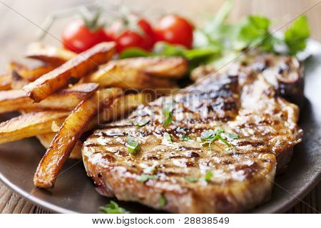 juicy grilled pork chop (neck cut) with greens