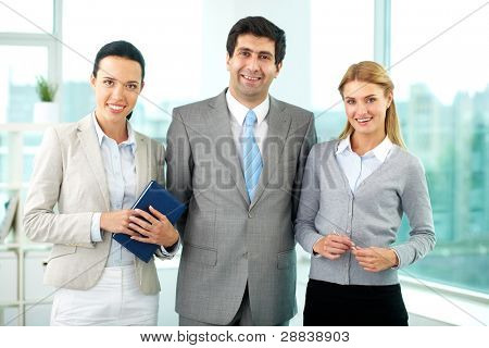 Three business people in formalwear looking at camera in office