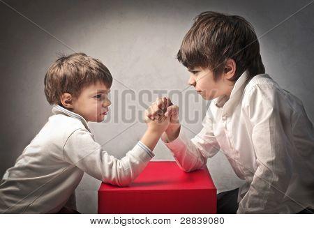 Two children doing arm wrestling