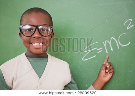 Schoolboy showing the the mass-energy equivalence formula on a blackboard