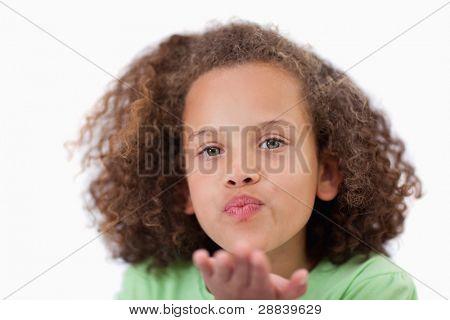Close-up de uma menina de soprar um beijo contra um fundo branco