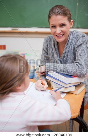 Portrait of a teacher explaining something to her pupil in a classroom