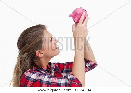 Woman looking inside a piggy bank against a white background