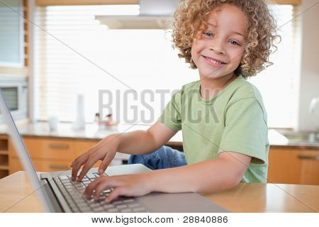 Boy using a laptop in a kitchen