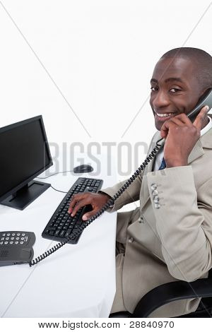Side view of a male secretary answering the phone while using a monitor against a white background