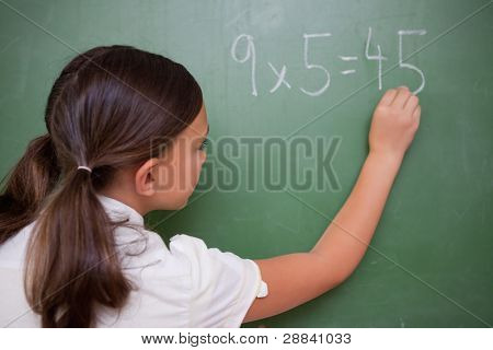 Schoolgirl writing a result on a blackboard