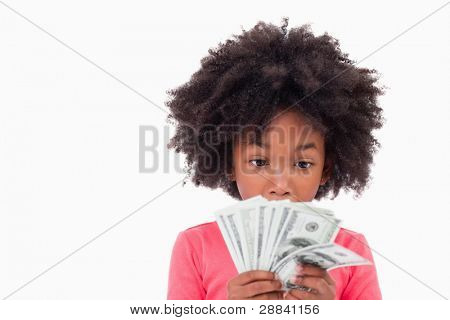 Girl looking at bank notes against a white background
