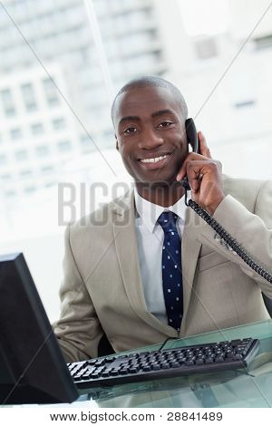 Portrait of a smiling office worker making a phone call  while using a computer