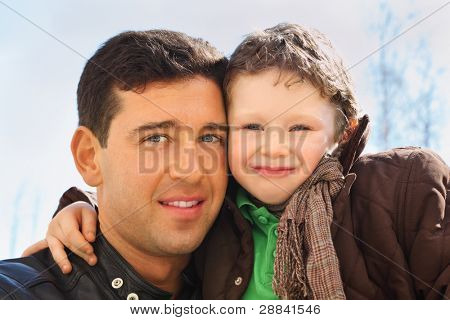 happy father and his little son wearing in jacket hug outdoor in spring